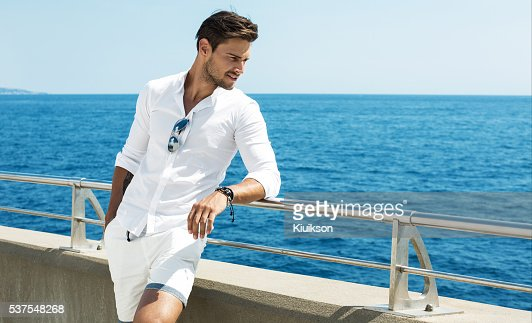 Handsome man wearing white clothes posing in sea scenery : Stock Photo