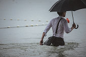 Rear view on a handsome man wearing white shirt and holding umbrella and a briefcase, running through the water on a rainy day. The man waded halfway in the water. Selective focus, three quarter lengt