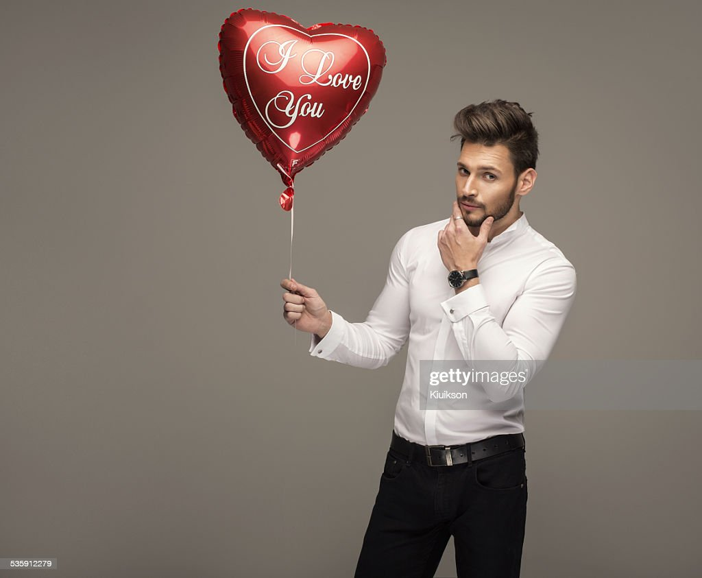 Handsome man with balloon heart thinking : Stock Photo