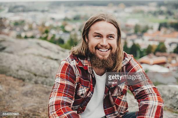 Gut aussehender Mann mit Bart im Freien in der Natur