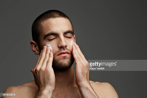 Handsome man with rubbing face cream on cheeks