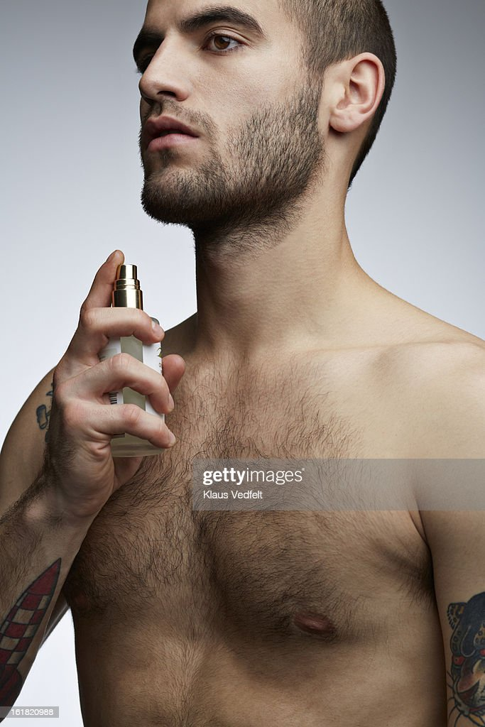 Handsome man with tatoo's spraying perfume on neck : Stock Photo