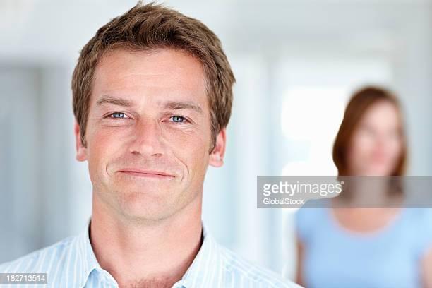 Un bell'uomo con la moglie in background