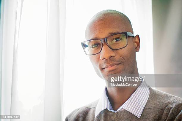 Handsome mature black male bald intellectual portrait by window