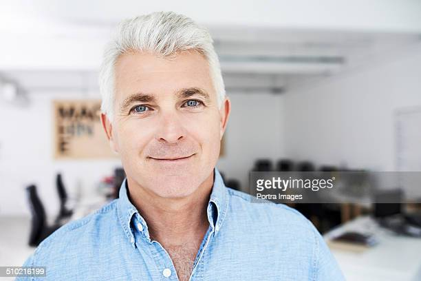 Handsome mature businessman smiling in office