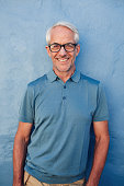 Portrait of handsome mature man with glasses looking at camera and smiling, he is leaning to against a blue wall.