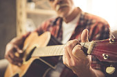 Cropped image of handsome mature man in casual clothes playing guitar at home
