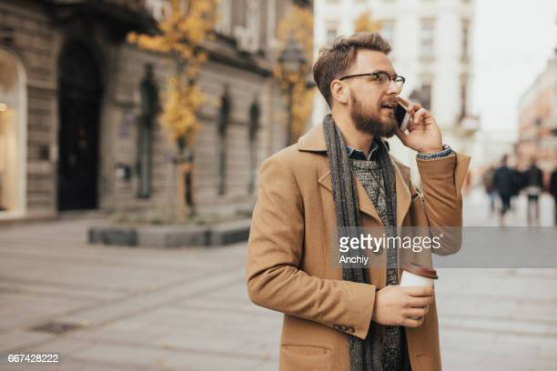 Handsome millennial downtown in one hand holding coffee cup and in another mobile phone