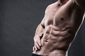 Handsome muscular bodybuilder posing on gray background. Low key studio shot with copy space. Sexy male body