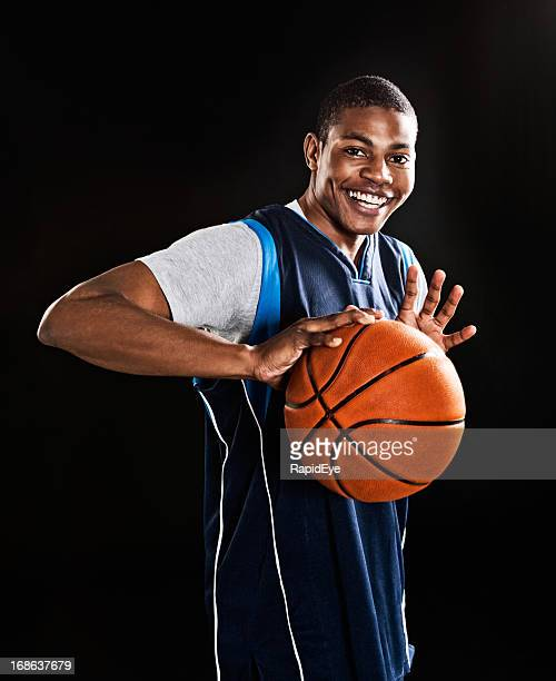 Handsome, muscular young basketball player smilingly prepares to play