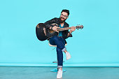 handsome bearded musician playing guitar over blue background. Full length man sitting on chair holding acoustic guitar