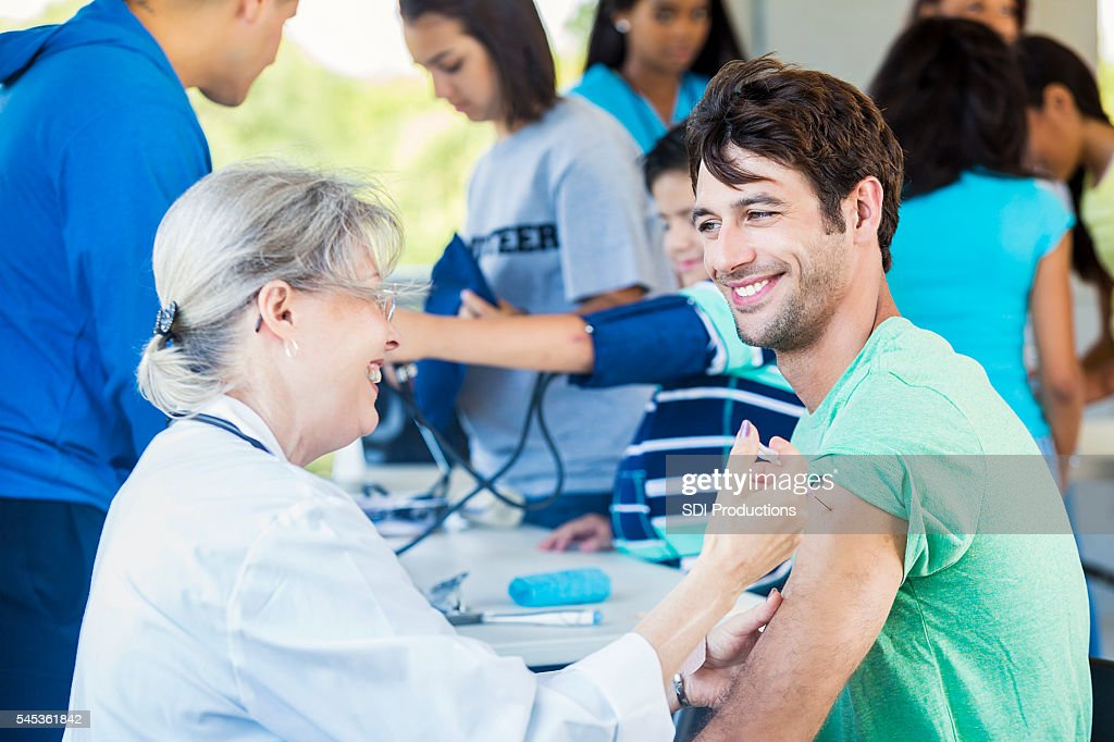Handsome patient smiling at doctor during vaccination