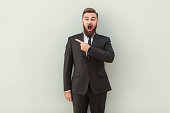 Handsome presenter of your advertisement. Happy young man in formalwear pointing away while standing against gray background. Studio shot.