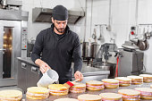 Handsome professional confectioner making a batch of delicious cake in the pastry shop .