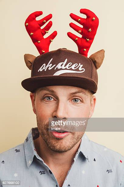 Handsome real man in christmas shirt and funny hat