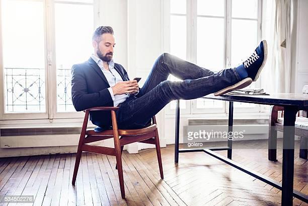 Détendue bel homme d'affaires regardant portable dans le bureau à domicile