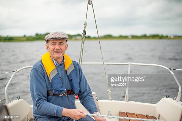 Handsome senior man sailing in the open waters