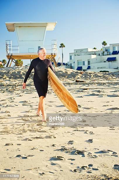handsome senior walking with longboard
