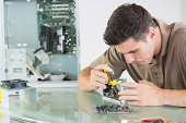 Handsome serious computer engineer repairing hardware with pliers in bright office