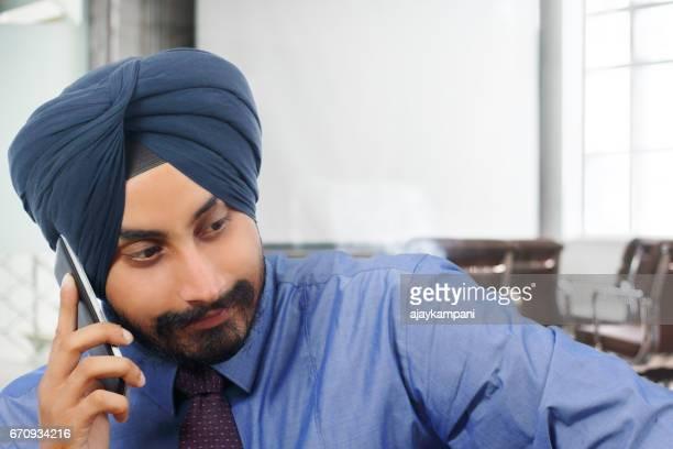 Handsome sikh businessman talking on phone