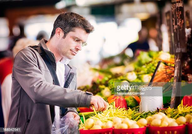 Handsome single man picking up string beans at market