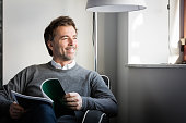 Handsome smiling man reading in a sofa looking at the window. He's reading a business plan at the hotel.