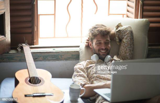 Handsome smiling man using laptop at home