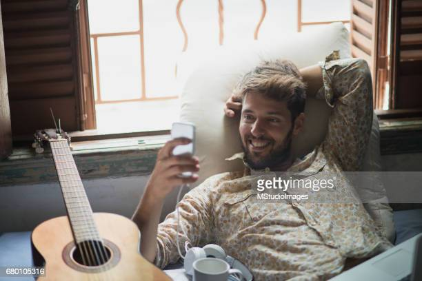 Handsome smiling man using mobile phone