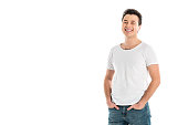 handsome smiling man with hands in pockets looking at camera isolated on white