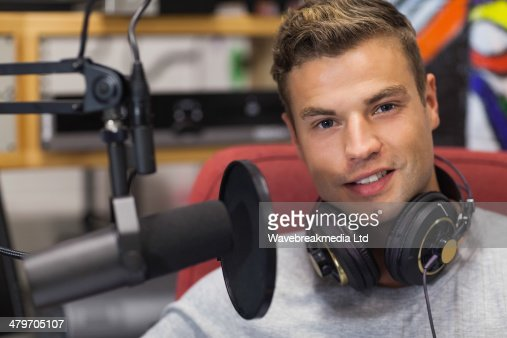 Handsome smiling singer recording a song : Stock-Foto