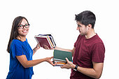 Handsome student couple exchanging bunch of books  isolated on white background