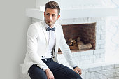 Handsome stylish man in white elegant suit sitting near fireplace