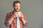 Handsome stylish young man in casual clothes is holding a cup of coffee, enjoying its aroma and smiling, on gray background
