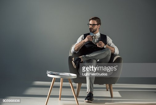 handsome stylish young man sitting in armchair and looking away while drinking coffee : Stock Photo
