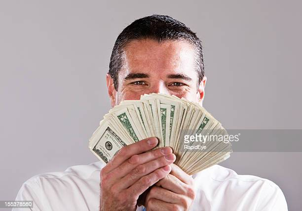 Handsome successful businessman with fistful of dollars smiles