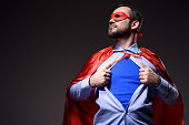 handsome super businessman in mask and cape showing blue shirt and looking away isolated on black