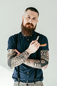handsome tattooed man holding razor and looking at camera