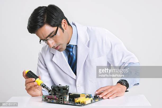 Handsome technician working on computer part against gray background