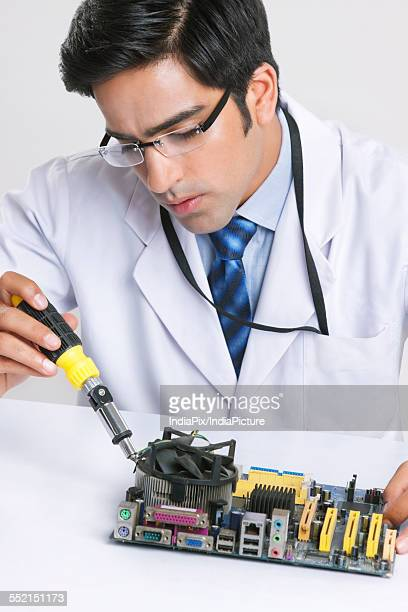 Handsome technician working on machine part against gray background
