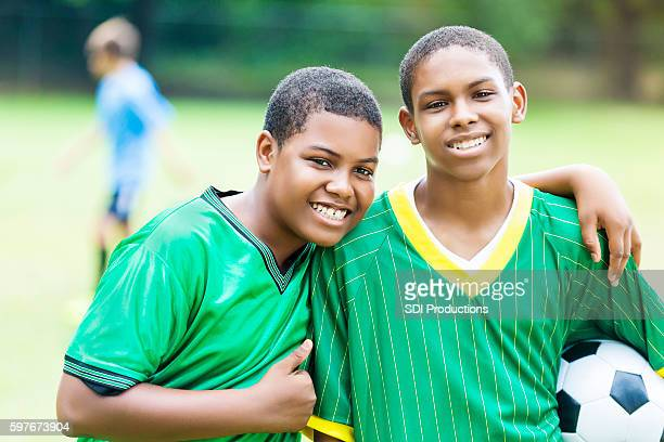 Handsome teenage soccer buddies smile proudly
