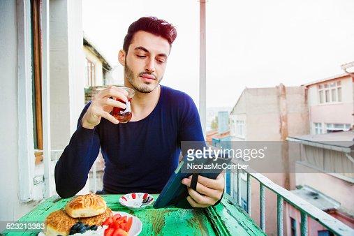 Handsome Turkish man enjoying media on his tablet during breakfast
