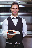 Handsome waiter holding a plate of squid ink spaghetti in the restaurant kitchen