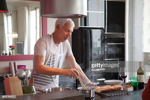 handsome white-haired mature male cooking at home in modern kitchen