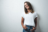 Beauty caucasian woman in white blank t-shirt, grunge wall, studio portrait