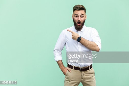 Handsome young adult man with beard in shoked. Pointing away while standing isolated on light green background : Foto de stock