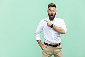 Handsome young adult man with beard in shoked. Pointing away while standing isolated on light green background