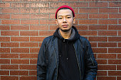 Handsome young asian man. Wearing black jacket and red beanie. looking at camera. Standing in front of brick wall