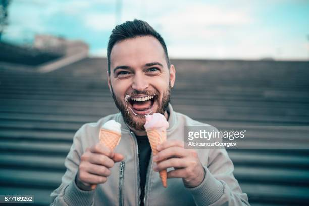 Handsome Young Boy Eating Ice Cream From Two Cones