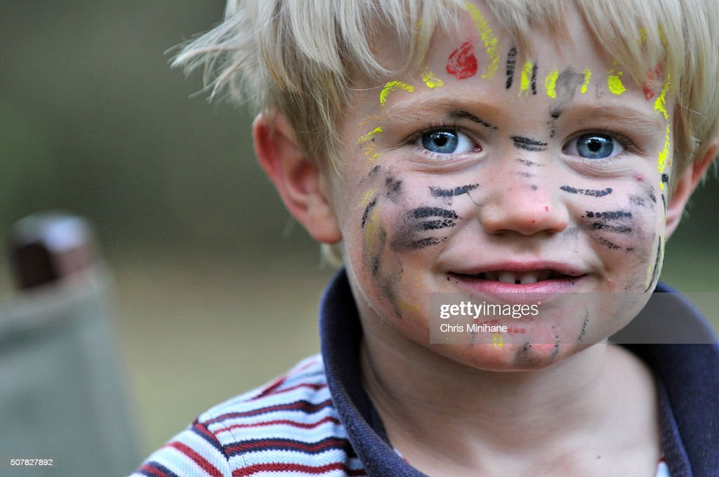 Handsome young boy smiles gently into the camera wearing facepaint.