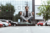 handsome young businessman floating in air in lotus pose and meditating at parking